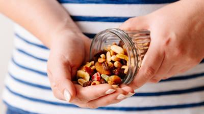 Hands pouring assorted nuts out of a jar
