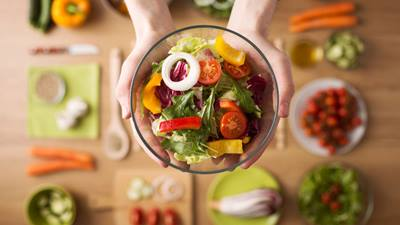 Hands holding a brightly colored salad