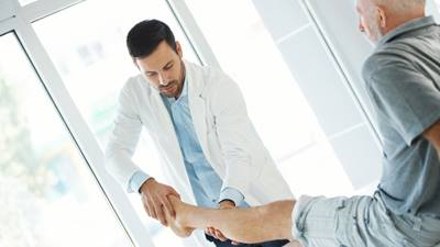 Male doctor examining male patients shin